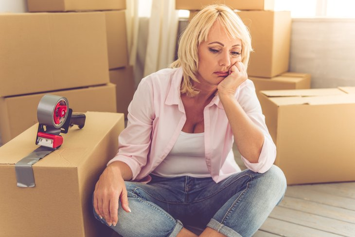 Upset woman packing moving boxes