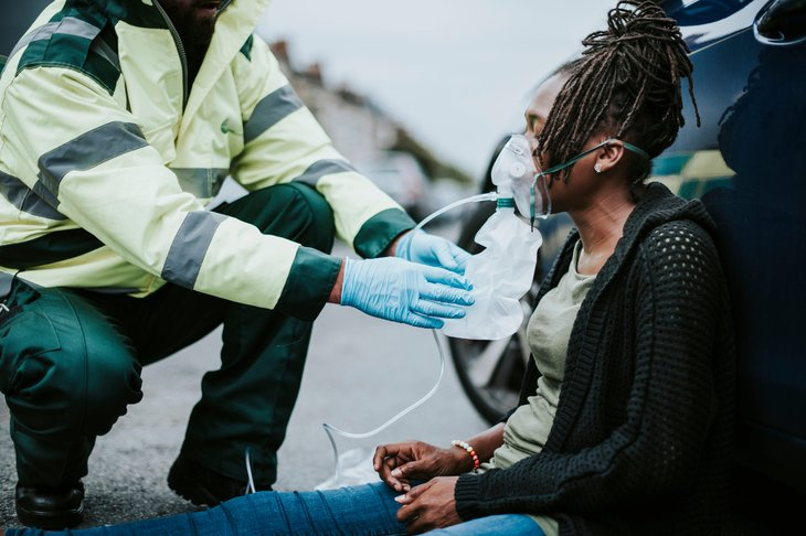 A paramedic treats an injured woman