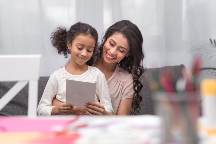 Mom and daughter with greeting card