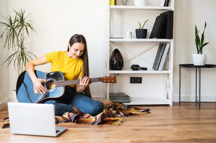 Woman playing a guitar for fun
