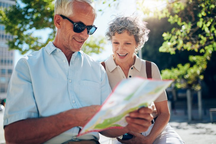 Happy retired couple looking at a map for their next destination