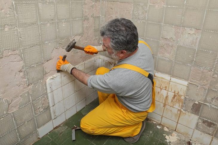 Older worker demolishing bathroom tiles