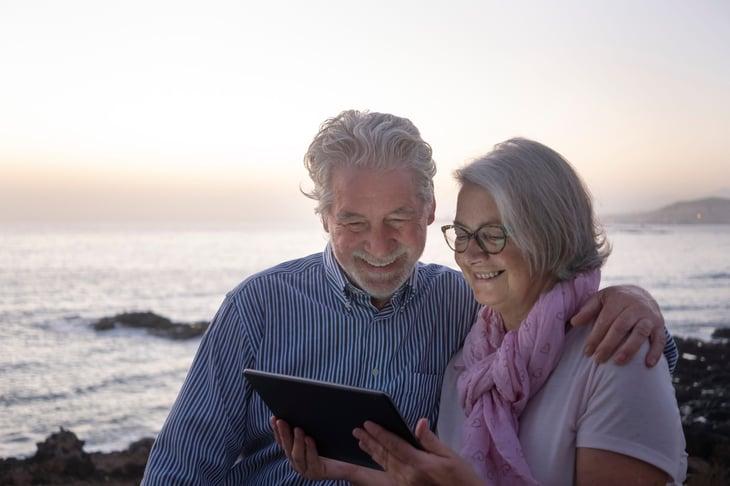 A senior couple looks at a tablet on the beach