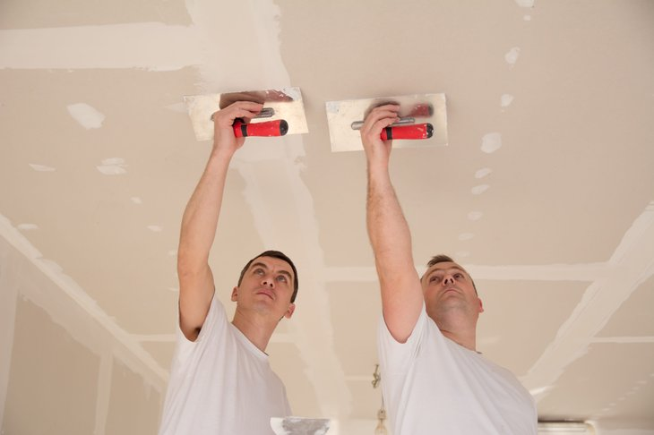 Workers plaster a ceiling