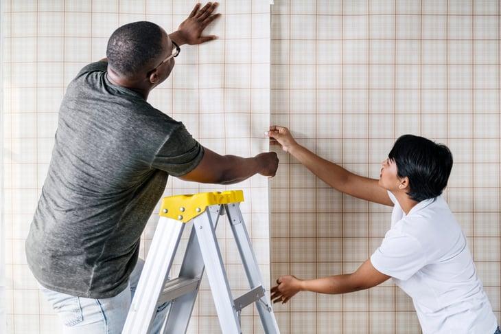 Men wallpapering a home