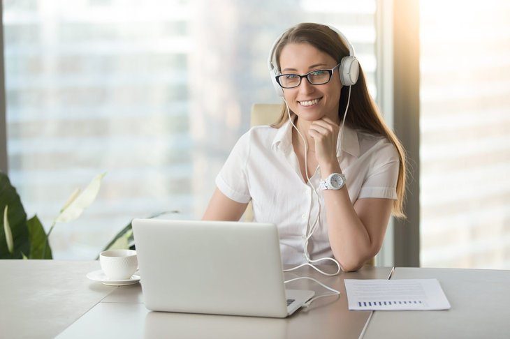 Young woman on laptop with headset