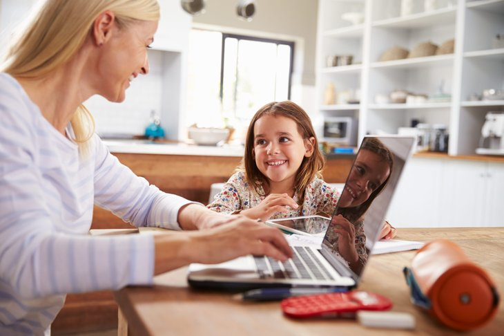 A mother working from home while her young daughter asks questions and interrupts