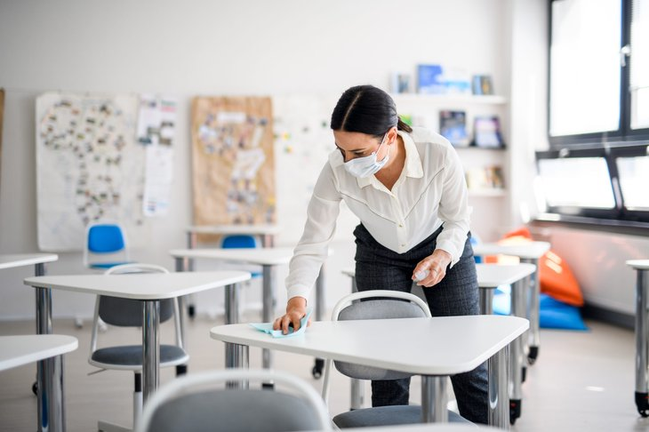 Teacher in a face mask disinfecting student desks