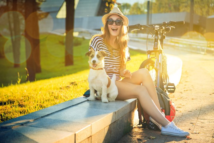 Happy Hipster Woman with her Dog and Bike in the City.
