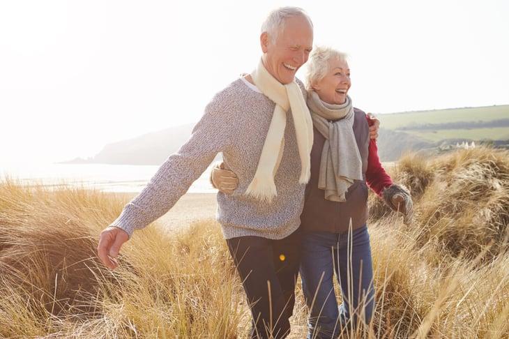 Happy senior couple walking on the beach grass