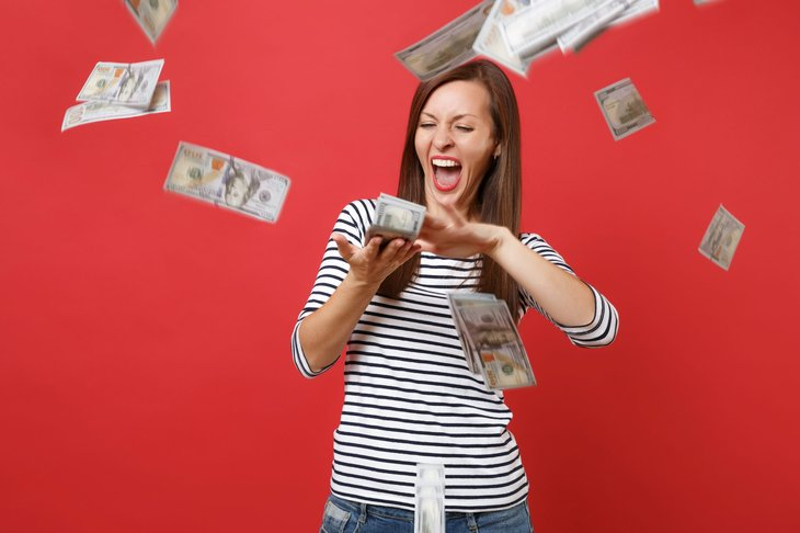 A happy woman who struck it rich throws cash around