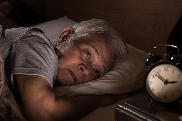 Older senior man can't sleep because of retirement stress