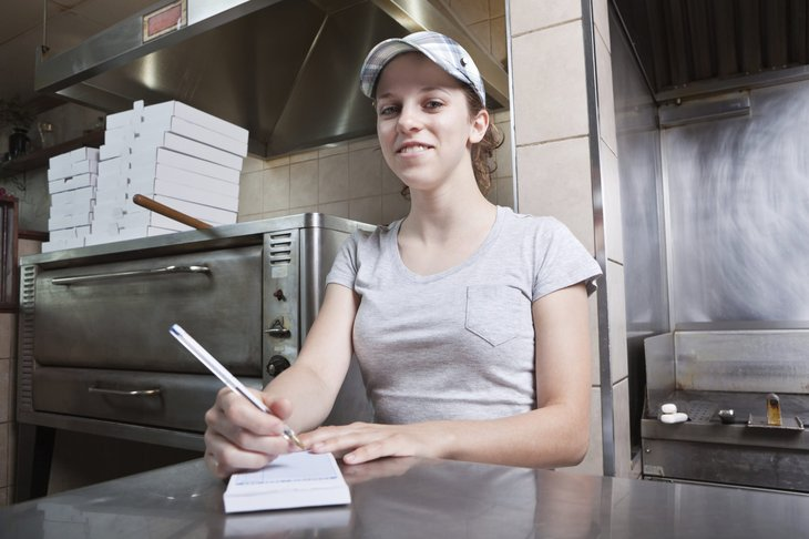 Young woman minimum wage worker taking order at a restaurant