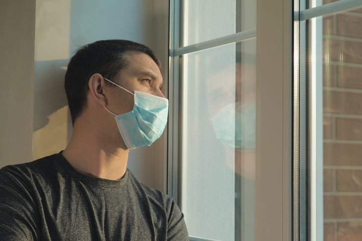 Worried man in a mask looking out a window while self-isolating