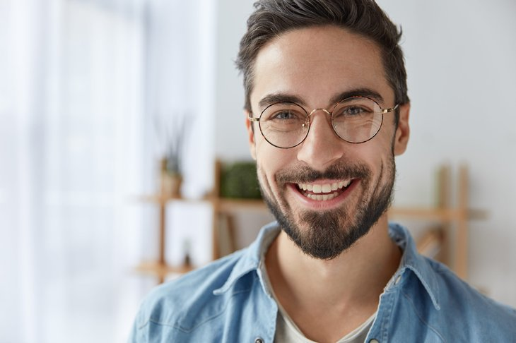 Happy young bearded guy with glasses