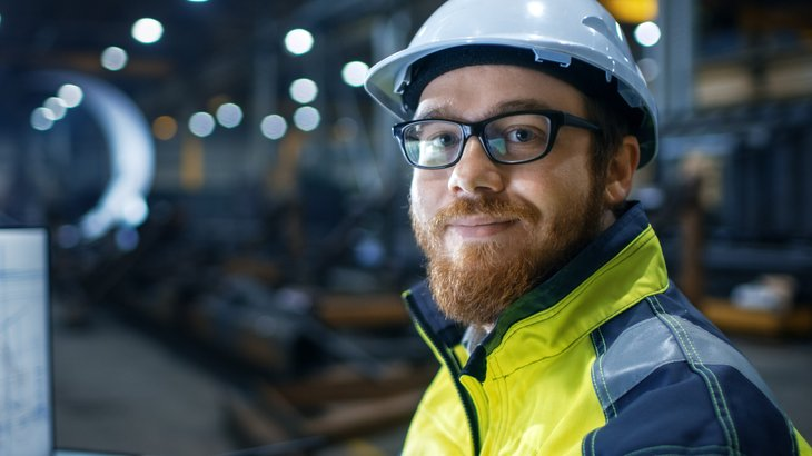 Industrial worker in hardhat working hard but smiling