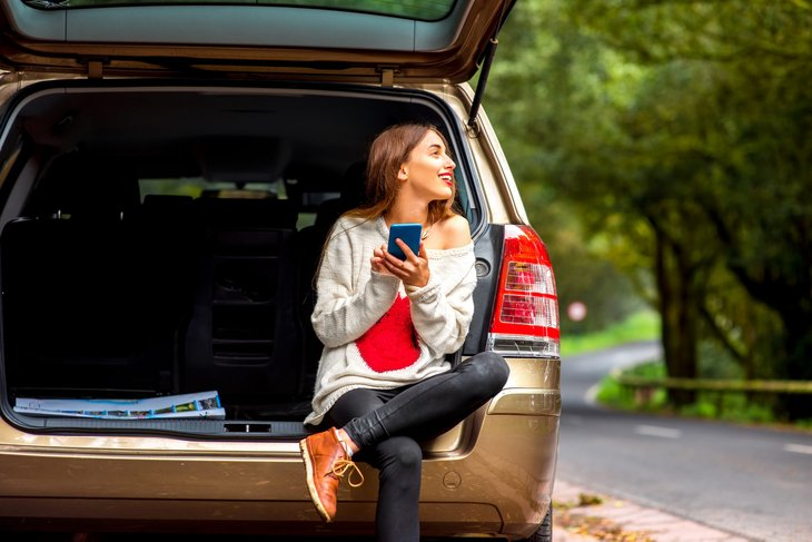 Woman using a smartphone in her car