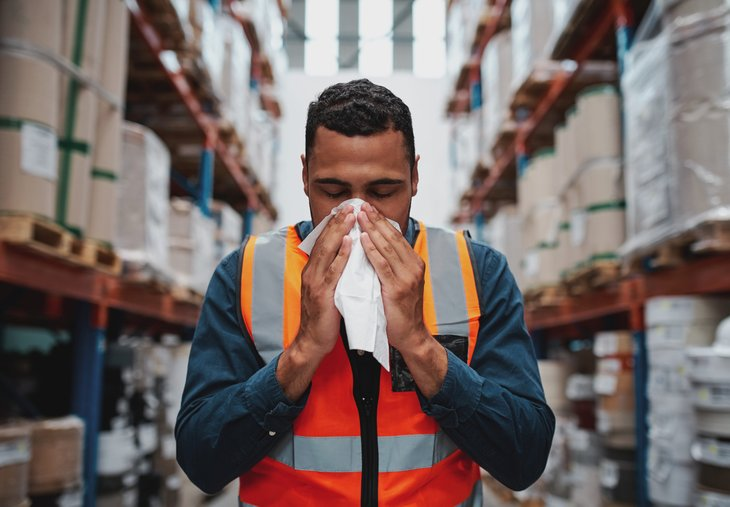 A sick warehouse worker blowing his nose