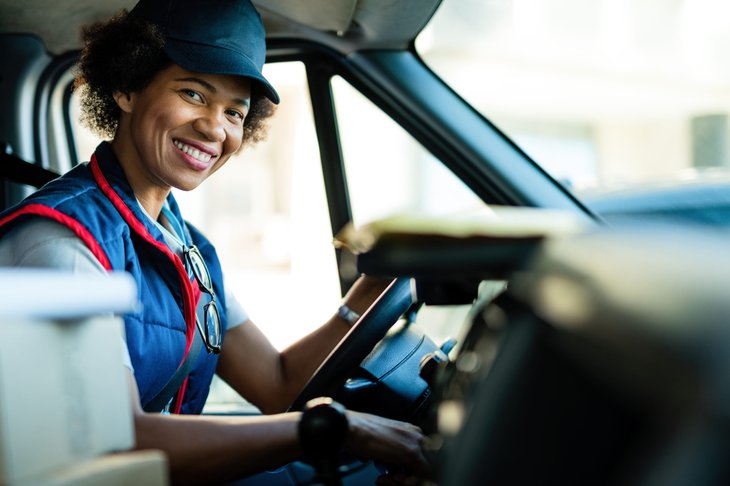 Female courier and package delivery driver in a truck
