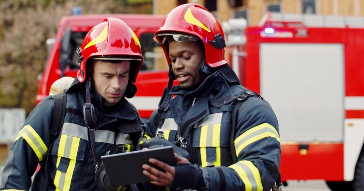 Firefighters examining fire reports on tablet