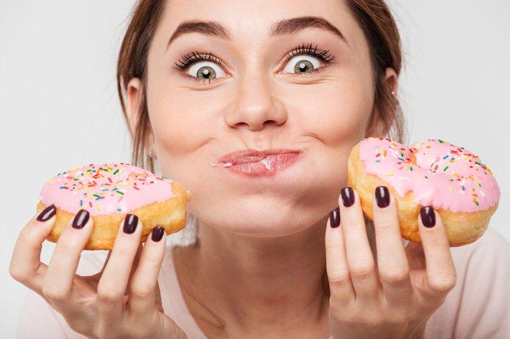 Woman eating glazed doughnuts