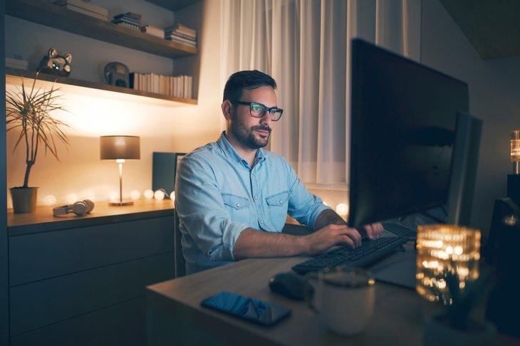 Man working remotely on computer at night