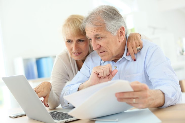 Senior couple studying retirement tax information online