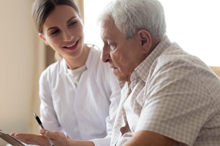 Senior filling out medical paperwork with caregiver