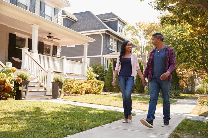 Millennial couple walking through their new neighborhood as homeowners