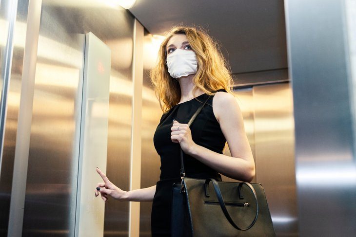 Businesswoman in a mask taking an elevator alone
