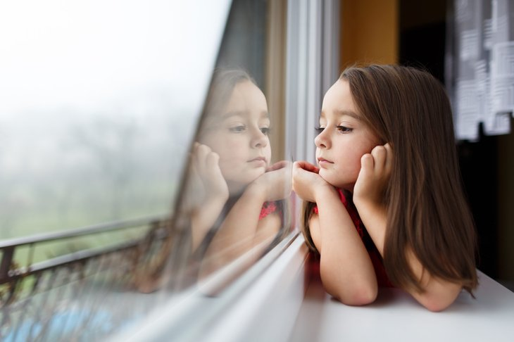 Young girl at window waiting for parents