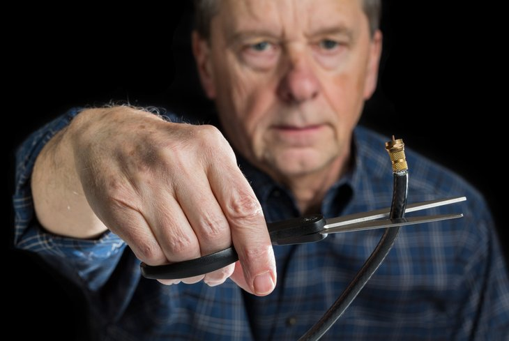 Older man cutting the cord and cancelling cable TV