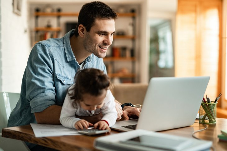 Father working from home on laptop with young daughter