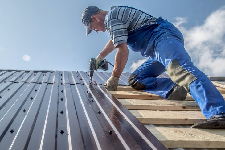 Construction worker installing a metal roof