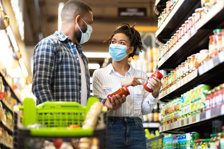 Couple in masks shopping for groceries