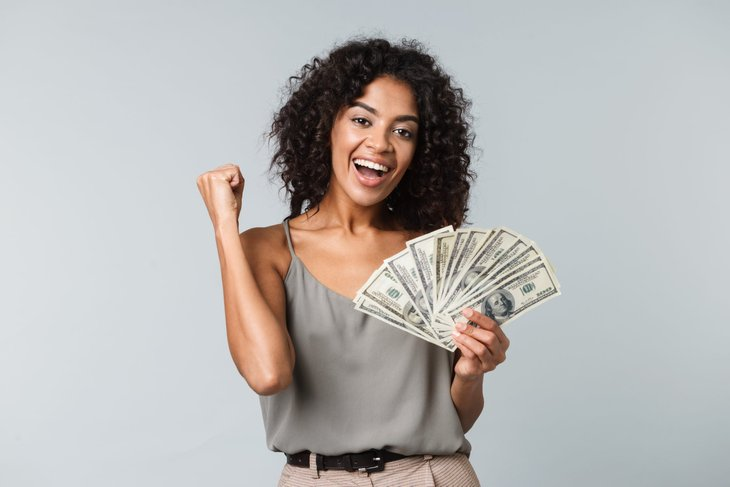 Young woman excited about handful of money
