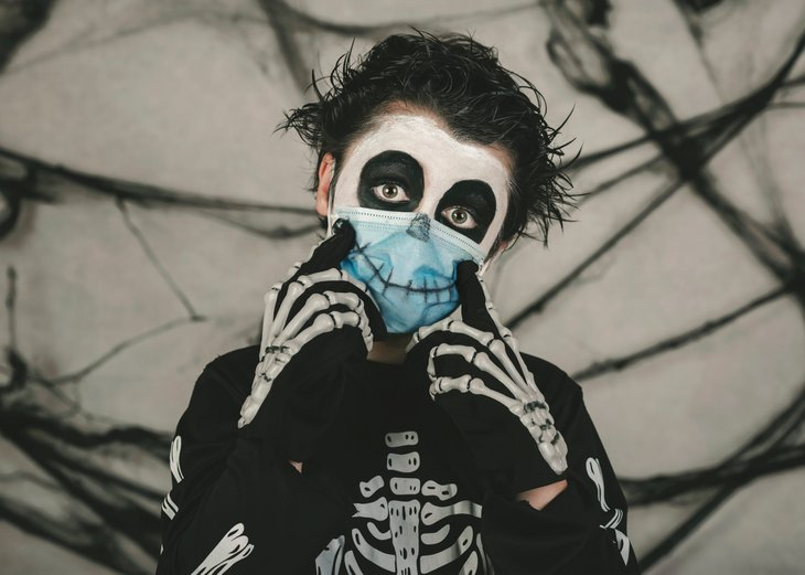 Boy in skeleton Halloween costume with face mask during the pandemic