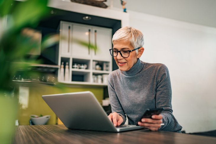 Senior woman working on laptop and phone from home