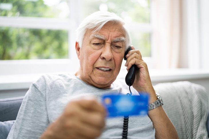 Senior man being scammed on the phone with credit card
