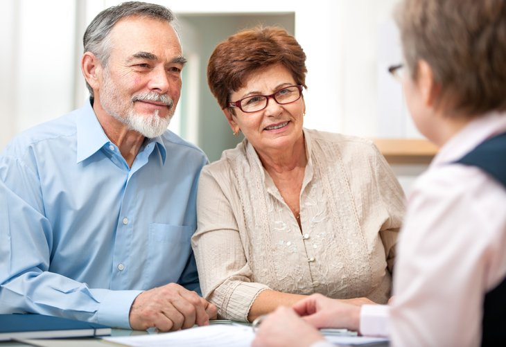 Senior couple making retirement plans with adviser
