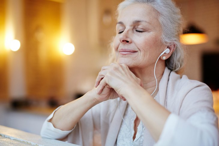 Senior woman relaxing in retirement with music