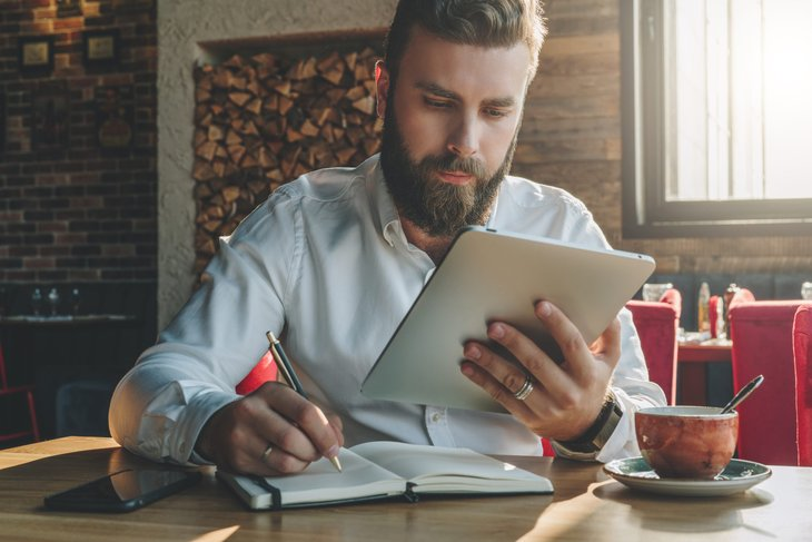 Bearded man studying investing basics on his tablet