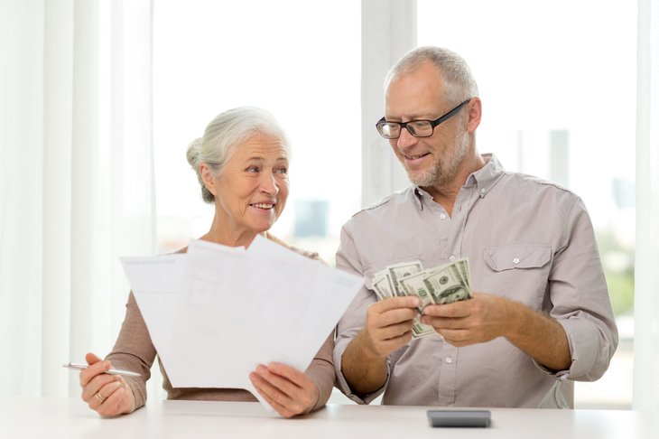 Seniors with money and paperwork