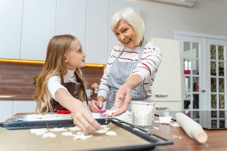 Grandmother baking cookies with her granddaughter
