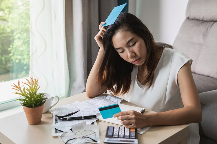 Stressed woman looking at bills and credit card