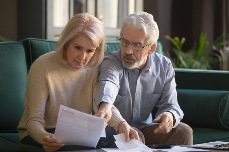 older couple reviewing finances confused