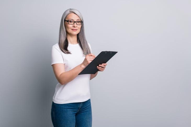 Senior woman using checklist and clipboard