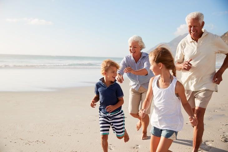 Retired senior couple running on the beach with grandkids