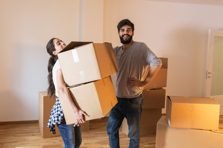 Man and woman couple carrying boxes preparing to move into new home
