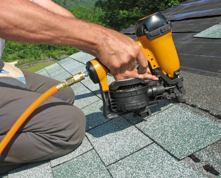 Man installing asphalt shingles on a roof